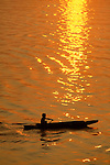 Silhouette of a young native boy paddling a wooden dugout canoe on the Amazon River lit with orange and yellow colors of the sunset in the waters around him, Brazil, South America.