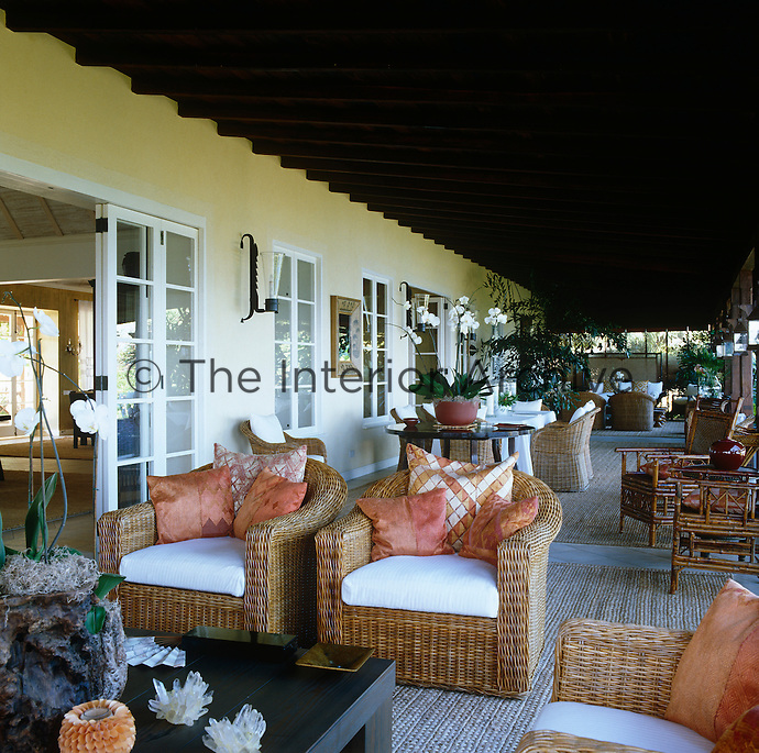 Combinations of wicker furniture create sitting and dining areas along this wide covered terrace