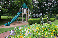 Kids backyard near garden, with tree house, sliding board, tiered plantings of petunias &nasturtiums, trees, shade, swings, boxwood, lawn