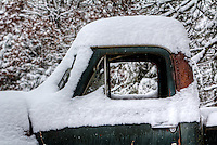 An old truck covered with snow during a snowstorm in rural arts West Arkansas.