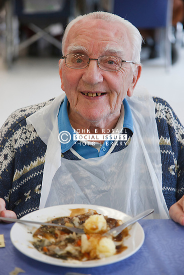 Elderly war veteran with shrapnel in brain having lunch at a resource for people with physical and sensory impairment.