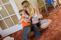 A woman sits crosslegged at home on the carpet of her living room floor breastfeeding her baby and kissing and cuddling her older boy at the same time.  <br /> <br /> 09/07/2011<br /> Hampshire, England, UK