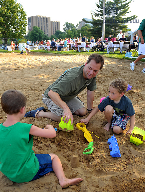 Food Services business manager Dave Dits enjoys the sand with his kids in the volleyball pit at Even Fridays picnic at Riehle Fields, August 14, 2009.