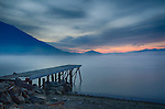 Idaho, North, Bonner County, Sandpoint, Sunnyside. A dock reaches through the morning fog towards approaching sunrise.