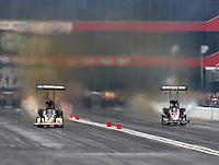 Jun 20, 2015; Bristol, TN, USA; NHRA top fuel driver Leah Pritchett (left) races alongside Terry McMillen during qualifying for the Thunder Valley Nationals at Bristol Dragway. Mandatory Credit: Mark J. Rebilas-