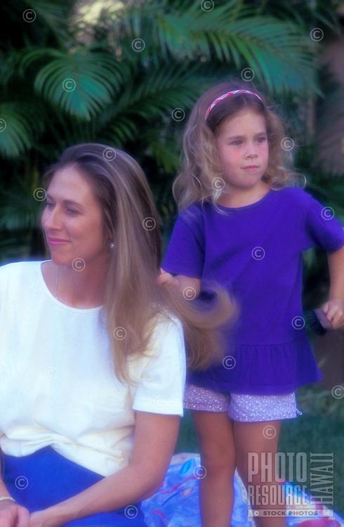 Girl brushing mom's hair