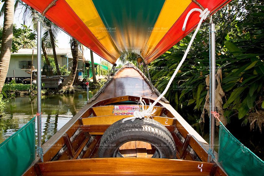 "Thailand. Bangkok. Long tail boat ride along the canal (Klong) Noi. The boat is usualy docked at a pier in Tha Tian. The long-tail boat is a type of watercraft native to Southeast Asia, which uses a common automotive engine as a readily available and maintainable powerplant. A craft designed to carry passengers on a river may include a lightweight long canoe hull, up to 30 meters, and a canopy. The sole defining characteristic is a secondhand car or truck engine. This engine is invariably mounted on an inboard turret-like pole which can rotate through 180 degrees, allowing steering by thrust vectoring. The propeller is mounted directly on the driveshaft with no additional gearing or transmission. Usually the engine also swivels up and down to provide a ""neutral gear"" where the propeller does not contact the water. The driveshaft must be extended by several meters of metal rod to properly position the propeller, giving the boat its name and distinct appearance. Control is achieved by moving the engine with a lever stick attached to the inboard side. Ignition and throttle controls provide simple means to control this simple craft. Tha Tian is a community located in the downtown area and in the center of the urban historic district, called Koh Rattanakosin. 29.03.09 © 2009 Didier Ruef"