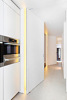 A modern kitchen with two full-height pivoting doors that separate the kitchen from the hallway.