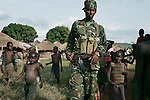 PAGAK, UGANDA AUGUST 5: A soldier from the Ugandan Army walks with children on August 5, 2005 in Pagak, camp for displayed people in northern Uganda. About 1.5 million people have fled villages and live in about 180 squalid Internally Displaced People (IDP) camps, which has changed rural life in Northern Uganda. .Many children in this area are afraid of being abducted by the Lord's Resistance Army (LRA). The rebel group has brought terror to Northern Uganda for almost twenty years, fighting the Ugandan government. The victims are usually children, which are abducted and used as child soldiers and sex slaves. (Photo: Per-Anders Pettersson)....