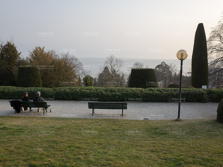 Switzerland. Canton Vaud. Lausanne. A couple seats on a bench in a park outside the Musée de l'Elysée. The man and the woman chat together, drink beers and enjoy a sunney spring afternoon with a view on the Genava lake. Lake Geneva (French: Lac Léman or Le Léman) is a lake on the north side of the Alps, shared between Switzerland and France. It is one of the largest lakes in Western Europe. 19.03.2015 © 2015 Didier Ruef