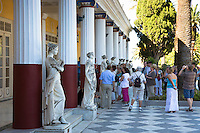Tourists view stone statues at Achilleion Palace, Museo Achilleio, in Corfu, Greece