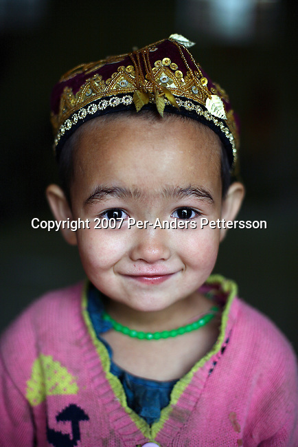 KHOTAN, CHINA - JUNE 18: A young Uygur girl poses for a photograph on June 18, 2007 in Khotan, China. She came with her family and thousands of villagers to a big traditional Sunday market to trade goods and meet people. Many are traditional people and dressed in traditional clothing. (Photo by Per-Anders Pettersson)..