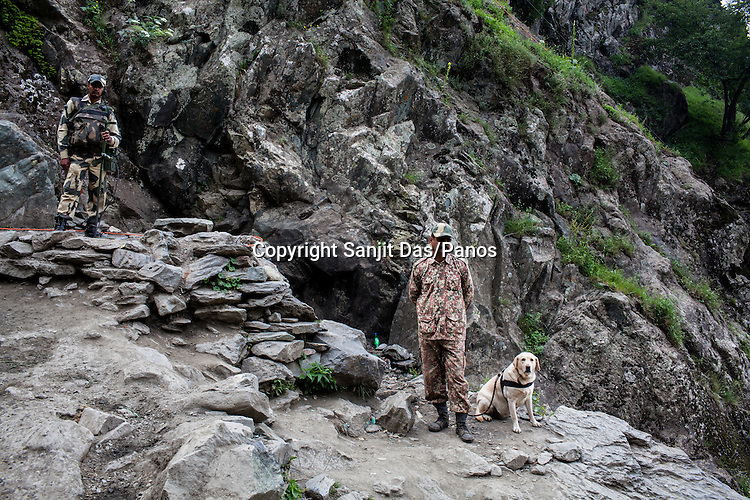 Security personnel seen with a sniffer dog, provide security along the Amarnath trekking route in Kashmir, India. Hindu pilgrims brave sub zero temperature and high latitude passes and make their pilgrimage to reach the sacred Amarnath cave, which houses a lingam - a stylized phallus, worshiped by Hindus as a symbol of God Shiva. Photo: Sanjit Das/Panos