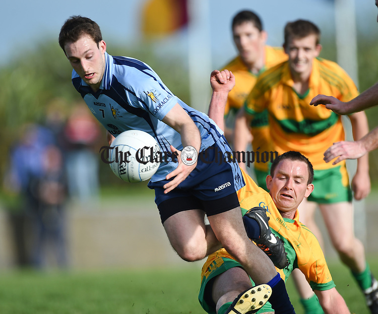 Thomas Donnellan of Cooraclare in action against Damien Carmody of O Curry's during their game in Doonbeg. Photograph by John Kelly.
