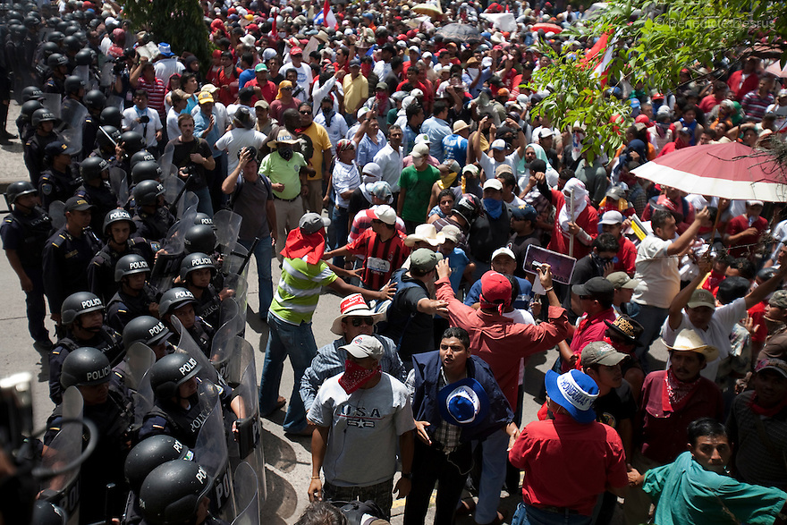 4 July 2009 - Tegucigalpa, Honduras  Thousands of supporters of Honduras' ousted president Manuel Zelaya try to break a police blockade as they march towards Toncontin international airport in Tegucigalpa, capital of Honduras. Zelaya has been forced into exile after being arrested by a group of soldiers in an apparent military coup. Zelaya was warned he would be arrested if he return to Honduras but has vowed to return to Honduras on Sunday accompanied by Latin American leaders. Photo credit: Benedicte Desrus