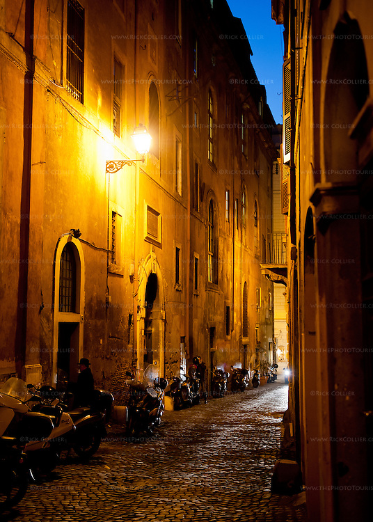 Cycles line a cobblestone street at night.  Rome, Italy.