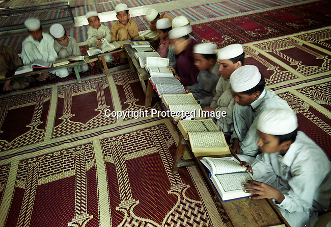 "Unidentified young boys reading the Koran at a Madrasa ""Koran school"" on September 24, 2001 in Rawalpindi 10 miles from Islamabad, Pakistan. The students, age 5-18 come from all over the country to live and study at the school. Many of these schools are recruiting grounds for the Taleban movement in Afghanistan, who are enforcing a strict law on the people of Afghanistan. (Photo: Per-Anders Pettersson)......"