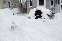 A woman shovels snow off a sidewalk next to a fire hydrant in Cambridge, Massachusetts, USA, on Saturday, Feb. 9, 2013, after Winter Storm Nemo hit the area.