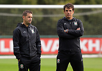 Pictured: (L-R) Coach Dr Adam Owen with manager Chris Coleman watch their players train. Monday 02 October 2017<br /> Re: Wales football training, ahead of their FIFA Word Cup 2018 qualifier against Georgia, Vale Resort, near Cardiff, Wales, UK.