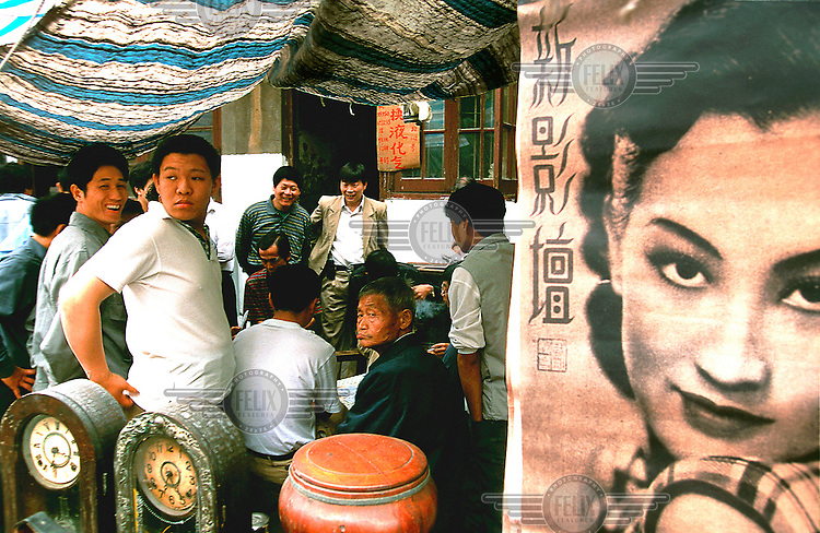 Mark Henley/Panos Pictures..China, Shanghai..Crowd around gambling card players at antiques market.