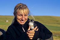 Ingrid N Visser holding newly fledged atlantic puffin, Fratercula arctica, Spitsbergen, polar high Arctic, Atlantic