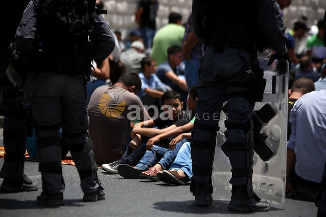 Israeli riot police (front) stand near Palestinians during Friday prayers on the street in the Ras al-Amud neighborhood in East Jerusalem, 20 June 2014. Israeli security forces limited attendance to Friday prayers in al-Aqsa Mosque to men over 50 in the belief clashes would start due to increased tensions and clashes since three Israeli teenagers went missing on June 12. Two Palestinians were killed in clashes in the West Bank early today. Photo by Saeed Qaq
