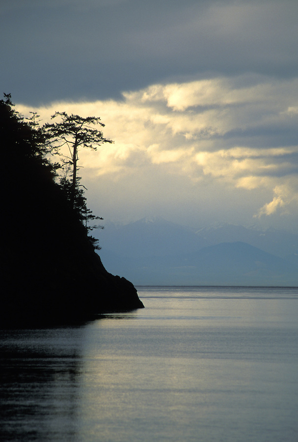 Coastal shoreline silhouetted against storm clouds with Olympic Mountains in background, Deception Pass State Park, Washington