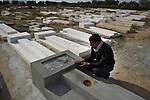 © Remi OCHLIK/IP3 - Sidi Bouzid Tunisia the 20 january 2011 - In the desert, close to Sidi Bouzid Walid, Mohamed Bouazizi 's cousin communes on Mohammed grave .When Mohamed Bouazizi set himself alight on Dec. 17, he sparked flames far greater than the ones that would ultimately kill him. The Tunisian man, an unemployed college graduate with children to feed, had tried finding work hawking vegetables, but was thwarted by police, who confiscated his cart. So in a grisly act of protest and anguish, Bouazizi doused himself in gasoline and set himself ablaze...The act of self-immolation not only triggered the current political crisis in Tunisia, which ousted the president Jan. 14 and has led to a complicated political impasse. It also inspired copycat self-immolations across North Africa, who attempted this very sensational form of suicide as statements of their own desperation and frustration with the authoritarian regimes in their countries. The latest count of protesters who have set themselves on fire in North Africa is up to eight, with four in Algeria, two in Egypt and one in Mauritania, as well as Bouazizi's act in Tunisia...