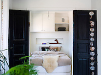 The bedroom 'unit', located in the middle of the apartment, is accessed through two rustic doors which have been smartened up with black paint