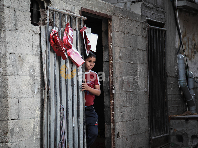 A Palestinian boy stands at the entrance of his family's home at al-Shati refugee camp, the third largest in the Palestinian Territories, in Gaza City on October 02, 2013. Photo by Ezz Zanoun