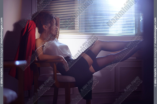 Artistic sensual portrait of a beautiful sexy woman sitting in a chair half undressed with her legs in stockings on a desk in dim night light coming from a shaded window