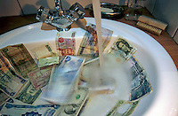 Washing international banknotes in a bathroom sink.