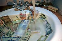 Washing international banknotes in a bathroom sink.