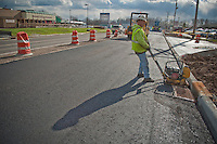 A construction worker compresses asphalt along the curb after the crew laid  asphalt on Westerville Road at Dempsey as roadway improvements near completion at the intersection. The changes are part of an improvement project at the I-270 interchange to upgrade the entrance road to Westerville, OH.