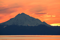 Mount Redout, an acitve volcano on the west side of Alaska's Cook Inlet, stands beautifully as the sun sets vibrantly behind the Aleutian Range.