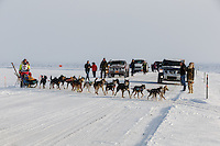 Monica Zappa on the trail just a few miles from the finish line crosses the road as spectators cheer her on as she nears Nome on Saturday March 15 during the 2014 Iditarod Sled Dog Race.<br /> <br /> PHOTO (c) BY JEFF SCHULTZ/IditarodPhotos.com -- REPRODUCTION PROHIBITED WITHOUT PERMISSION