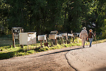 An older couple walks by a row of mailboxes on a road near Marble, Colorado