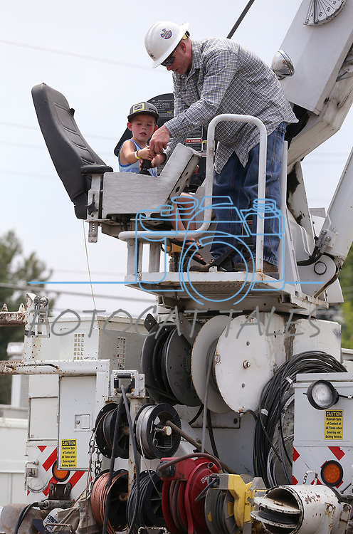 Scott Lawlor, with NV Energy, shows Cole Millim, 4, the controls of a crane during the Touch-a-Truck event at the Carson City Library in Carson City, Nev., on Saturday, Aug. 5, 2017. <br /> Photo by Cathleen Allison/Nevada Photo Source