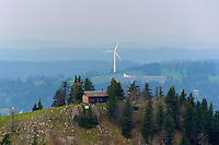 Small cabin on a mountain ridge with wind turbine in distance