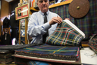Il proprietario del negozio sfoglia i campionari di tessuti tartan The owner of the shop with th different tartan tissues