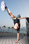 B-Boy Lilou pulling a move pose on Hong Kong's Victoria Harbour waterfront.