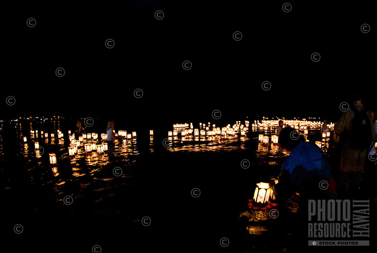 Family and friends continue to help usher out paper lanterns at the annual bon dance and Toro Nagashi (ìfloating lanterns set out to seaî) ceremony in Haleiwa. Inscribed with the names of the departed, the lanterns ride the outgoing tide to greet vi