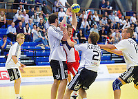 11 JUN 2010 - LONDON, GBR - Great Britain captain Ciaran Williams (red) finds himself stopped by the Estonian defence (white and black) during the 2012 European Handball Championships Qualification Tournament match between the two teams .(PHOTO (C) NIGEL FARROW)