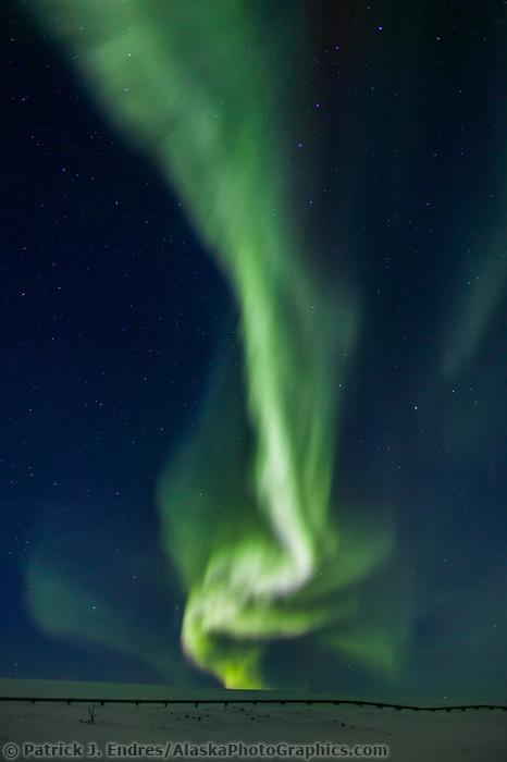 Aurora borealis streams down over the trans Alaska oil pipeline in the Arctic coastal plains, Arctic Alaska.