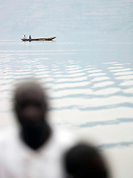 Man paddling in a small rowing boat on Lake Bunyonyi in South Western Uganda