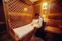 A Steward of the Eastern & Oriental Express preparing a bed in a State Compartment.