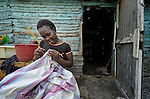 A woman sews in Batey Bombita, a community in the southwest of the Dominican Republic whose population is composed of Haitian immigrants and their descendents.