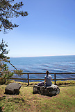 USA, California, Big Sur, Esalen, a woman rests on a rock and enjoys the view of the Pacific Ocean