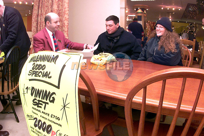 Shirley and Nigel Fulham from Donore pictured recieving their dining set from Pat McCormac, manager Wogans. Pat and Shirley waited outside Wogans from six o'clock the previous evening to recieve the Millenium 2000 Special dining set for only 2,000p..Picture Paul Mohan Newsfile