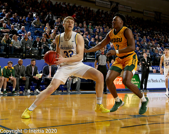 BROOKINGS, SD - JANUARY 22: Matt Dentlinger #32 of the South Dakota State Jackrabbits drives to the basket against Tyree Eady #3 of the North Dakota State Bison at Frost Arena on January 22, 2020 in Brookings, South Dakota. (Photo by Dave Eggen/Inertia)